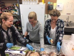 Three members of the Melton Foundation volunteering packing baked goods at the Edmonton Bissel Center.