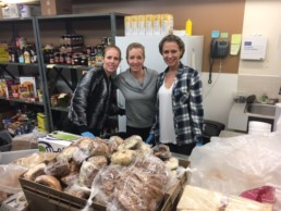 Three woman in hair nets baking good for the Edmonton Bissel Center. The Melton Foundation Members Volunteering around the city.