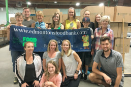 The Melton Foundation team at the Edmonton Food Bank. Volunteers posing with a banner.