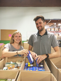 Man and woman packing food bank hampers. The Melton Foundations project with the Edmonton Food Bank.