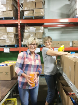 Two women packing boxes at volunteer warehouse. Charity. The Melton Foundation Charity work at The Edmonton Food Bank.
