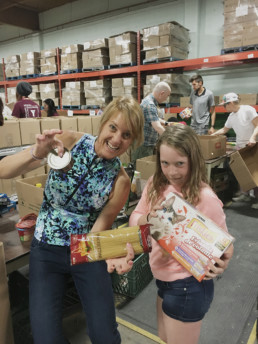 Woman and girl volunteer posing with food donations. The Melton Foundation at the Edmonton Food Bank.