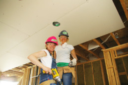 Two women in hard hats standing on ladder with construction tools on site. The Melton Foundation Habitat for Humanity project.