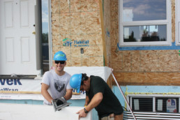 Two men in blue hard hats smiling and working on home construction. The Melton Foundation Habitat for Humanity Charity project for Habitat for Humanity.