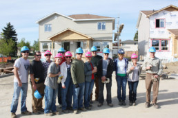 Group of people in hardhats smiling infront of habitat for humanity project. The Melton Foundation charity work.