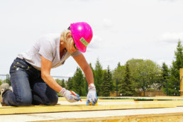 Woman in pink hard hat kneeling and measuring and marking wood on construction project. The Melton Foundation Habitat for Humanity project.