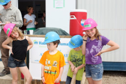 Kids smiling with hard hats infront of Habitat for Humanity Banner. The Melton Foundation in Action.