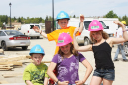 Kids smiling in hard hats posing with their muscles on construction site. The Melton Foundation Habitat for Humanity Project.