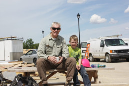 Older man sitting on picnic table with little boy smiling. The Melton Foundation Projects with Habitat for Humanity.