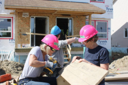Women in pink hard hats, woman drilling into board the other woman is holding at construction site. The Melton Foundation Project with Habitat for Humanity.