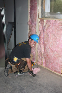 Man in blue hard hat smiling inserting home insulation. Habitat for Humanity project by The Melton Foundation.