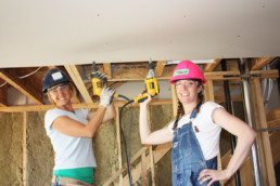 Two woman in hard hats on ladders holding drills up and smiling in construction site. Habitat for Humanity Charity project The Melton Foundation.