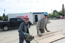 Man and woman with colorful hard hats smiling with saw and wood on construction site. The Melton Foundation Habitat for Humanity charity project.